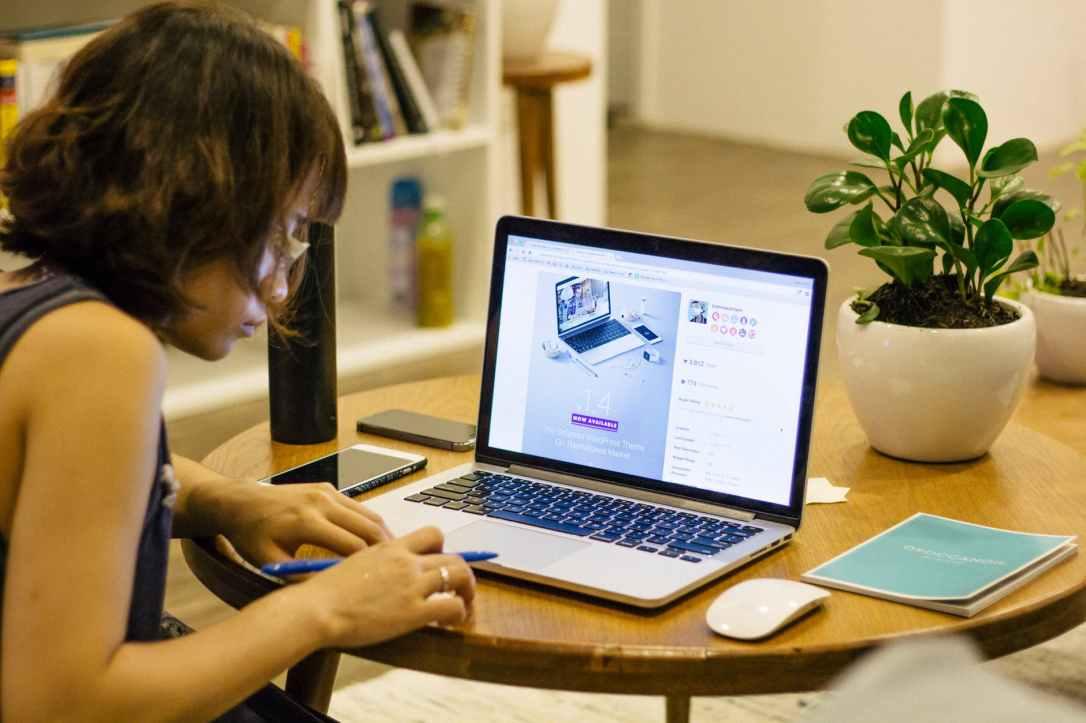 woman desk macbook pro pen